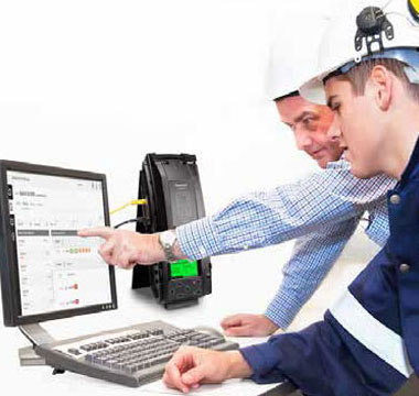 Two workers looking at computer, and IntelliDox is beside it